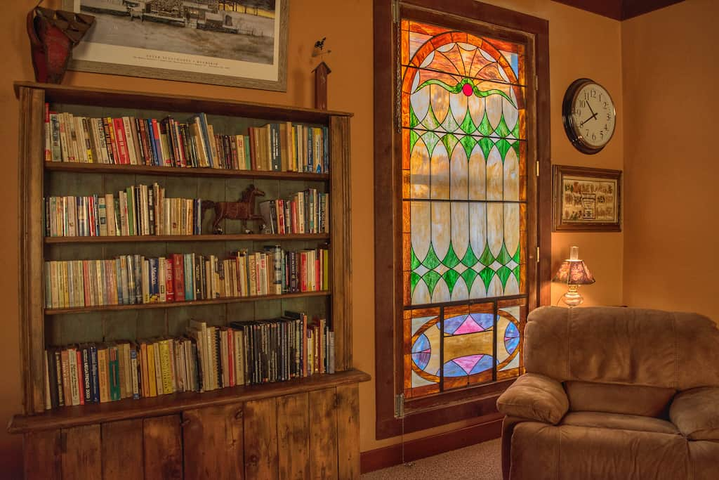 a cozy recliner next to a stained glass window?