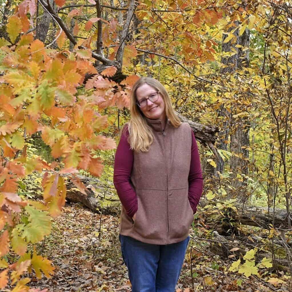 Profile Image of Tara Schatz surrounded by fall foliage.