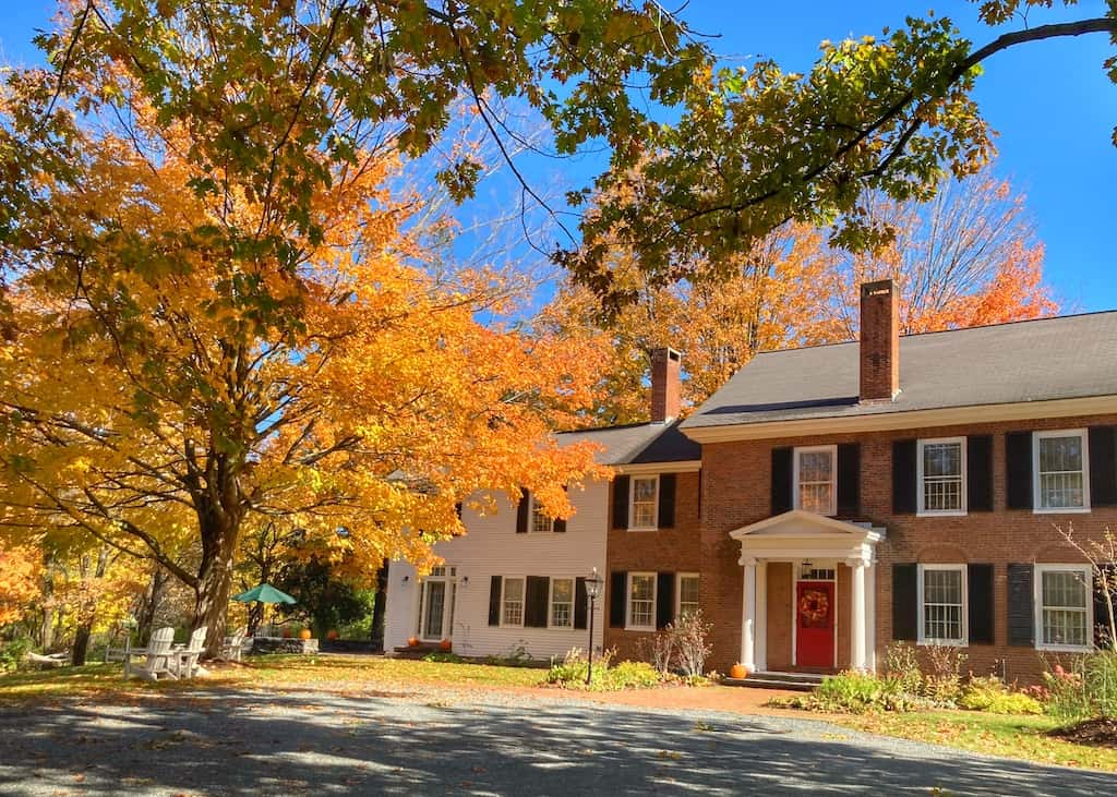 A historic home in downtown Woodstock, Vermont surrounded by fall foliage.