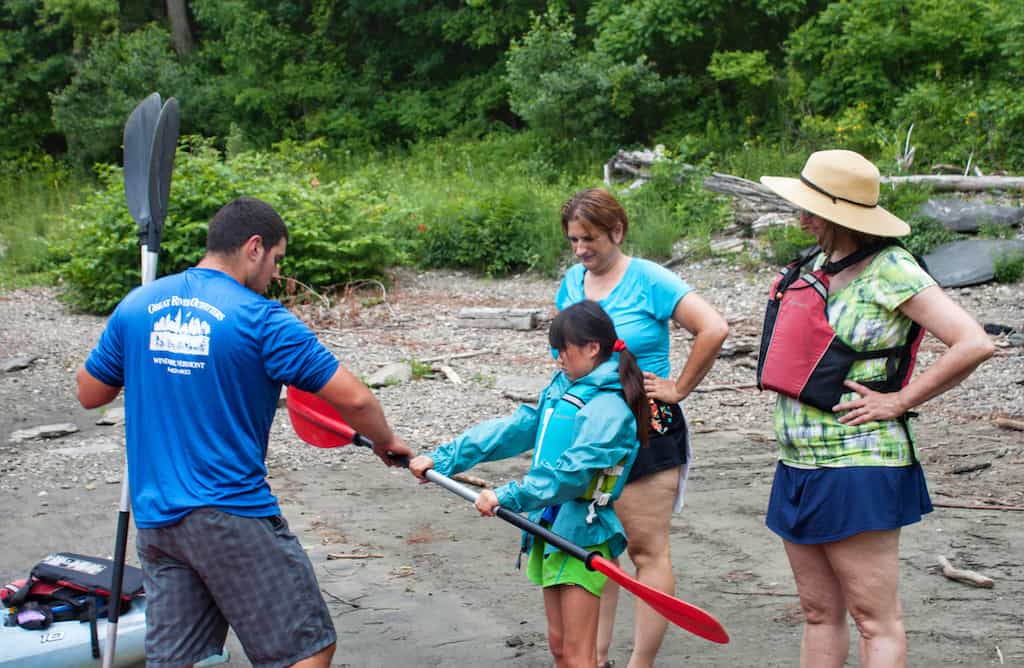 A man from Great River Outfitters shows us how to hold a kayak paddle.