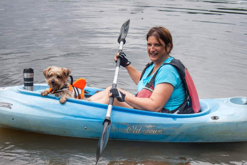 A woman and her small dog launch a kayak onto the Connecticut River.