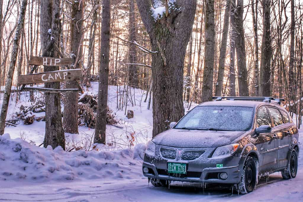 a grey Pontiac Vibe parked in the snow next to a Hipcamp sign.