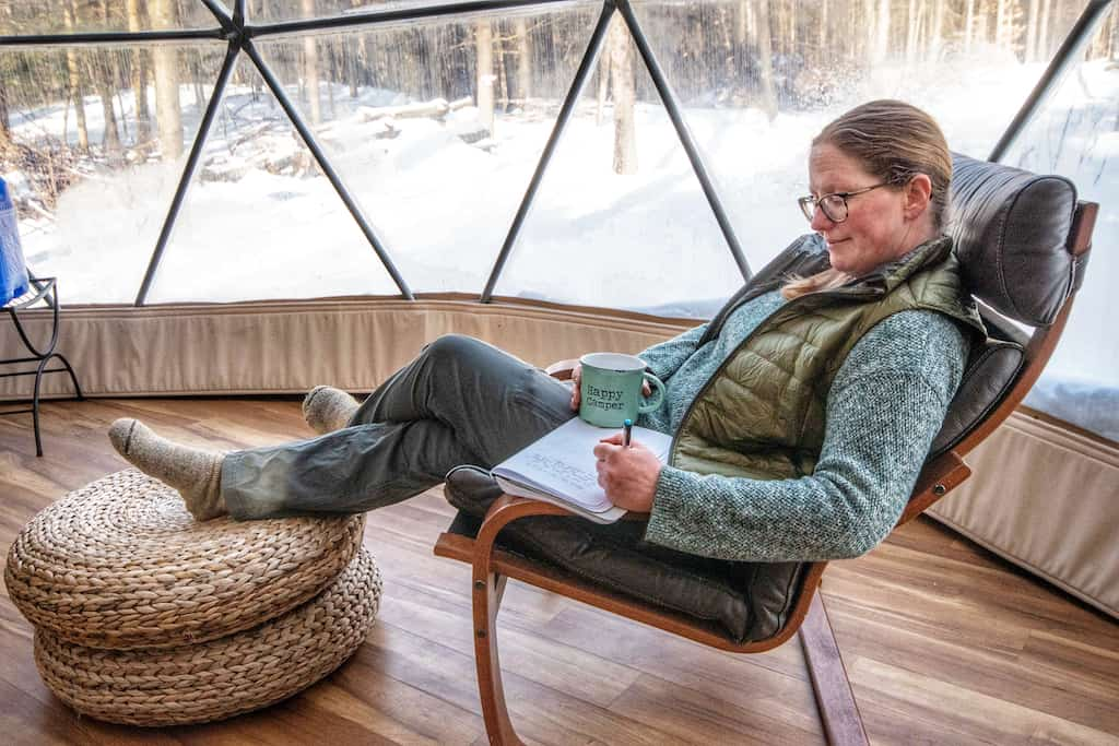 I'm relaxing in a chair writing in my notebook near the window of the geodesic dome.