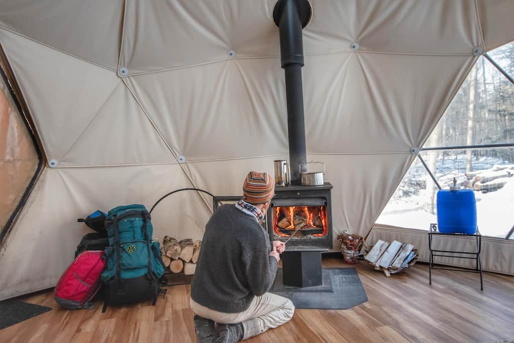 loading the woodstove in the geodesic dome.