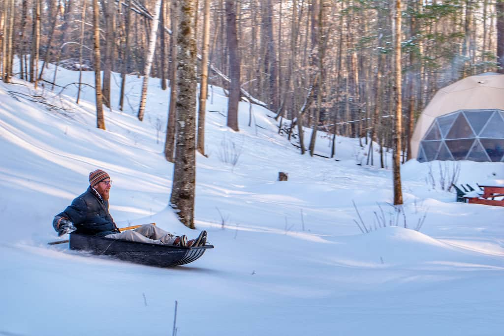 Eric sleds down the hill near our glamping dome.