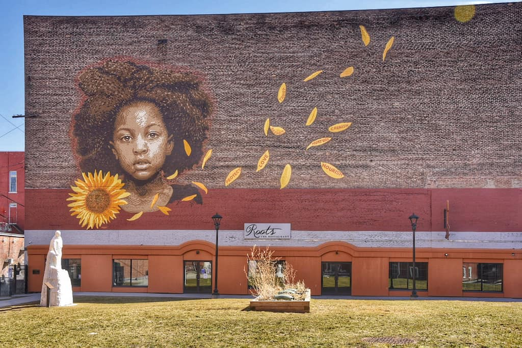 """A mural of a girl next to a sunflower called """"We Who Believe in Freedom Cannot Rest Until it Comes"""" in Rutland, Vermont."""