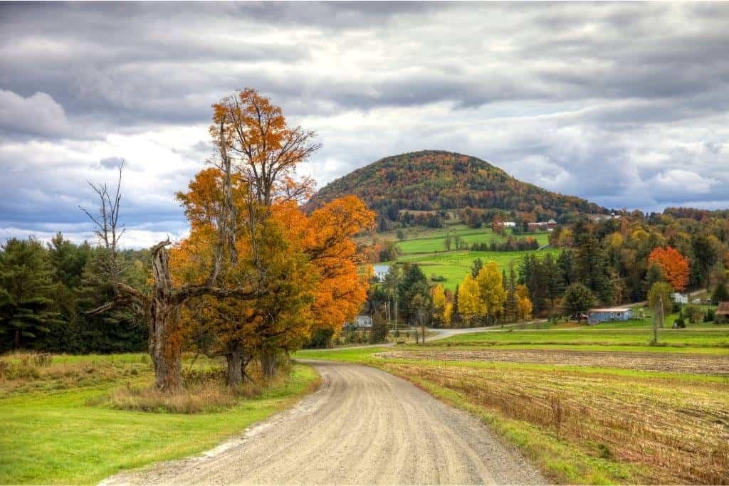 A dirt road through farmland in Vermont during fall foliage.