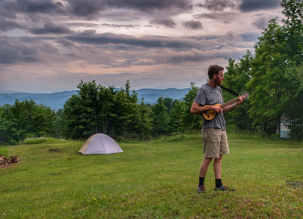 Eric playing his travel guitar as the sun goes down at Mountain Home Tent sites in Tunbridge, Vermont.