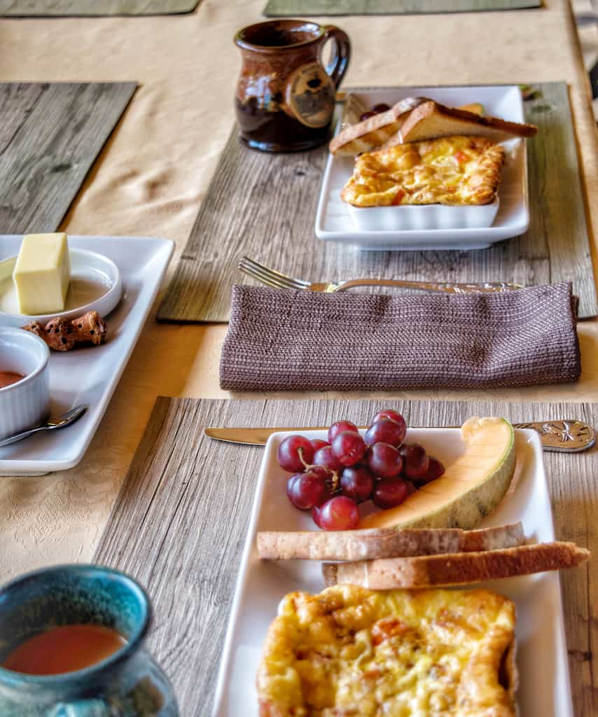 An outdoor breakfast table setting at Moose Meadow Lodge and Treehouse, featuring omelettes, toast, fresh fruit, and coffee.