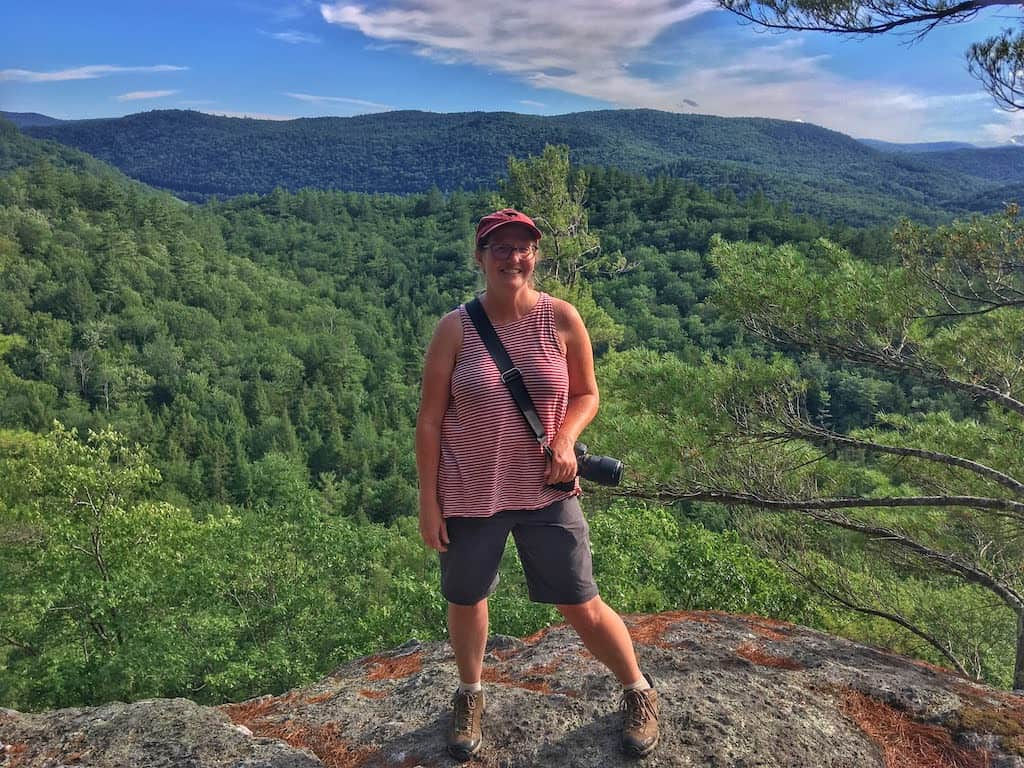 A woman stands at the top of Little Ball Mountain in Jamaica State Park Vermont. She is wearing shorts and a t-shirt and has a camera strapped around her neck.