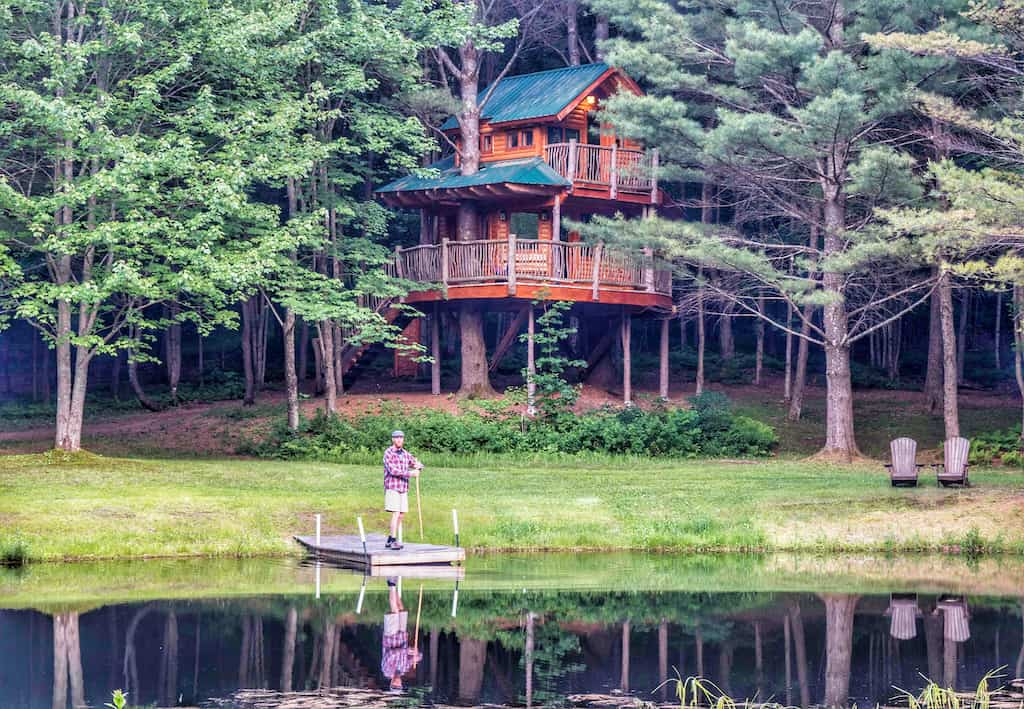 A man stands on a dock in the middle of a pond in front of a Vermont treehouse.