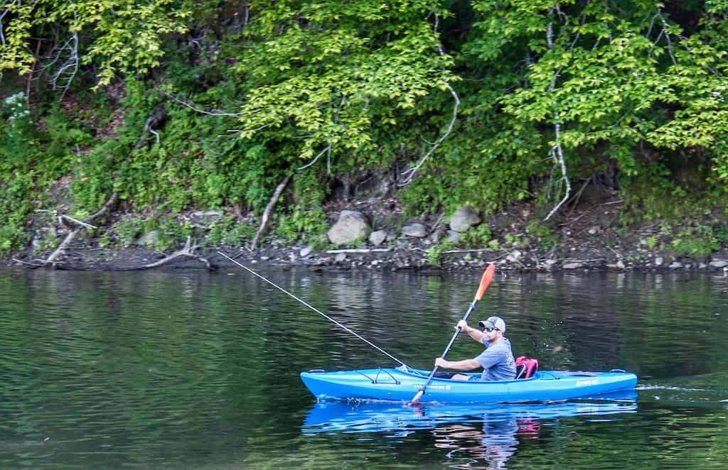 A man paddles a kayak in Waterbury Reservoir while fishing for trout in Vermont.