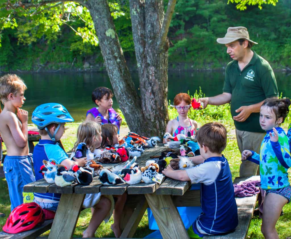 A park interpreter talks with a group of kids about bird migration at Little River State Park in VT.