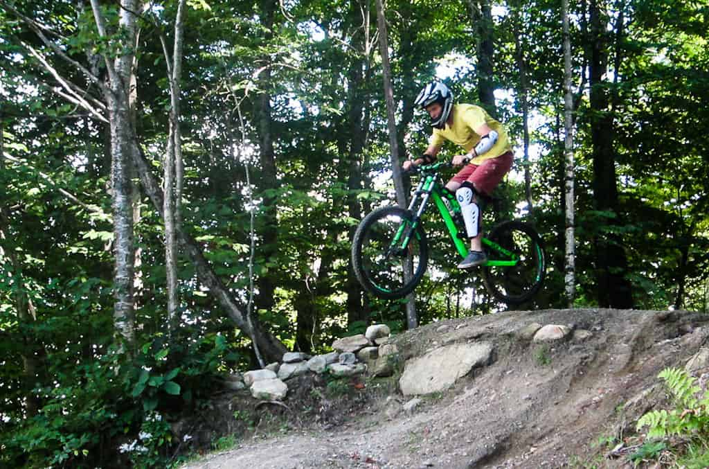 A teenager riding over a jump on the mountain bike trails at Mount Snow.