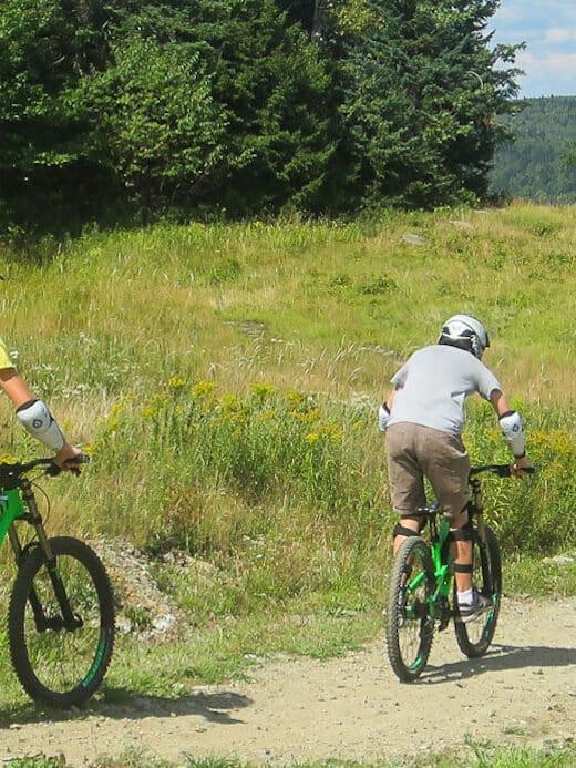 two boys riding mountain bikes at Mount Snow in Vermont.