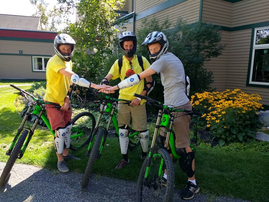 3 guys stand over rented mountain bikes at Mount Snow in West Dover, Vermont.