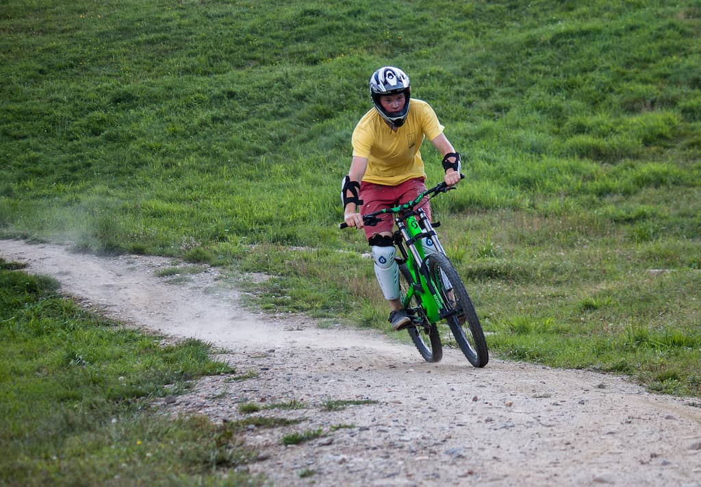 A young man rides a mountain bike on a dirt trail in Vermont.