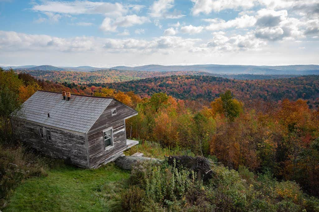 A view of an old cabin perched on the side of a mountain in Wilmington, Vermont during fall foliage season.