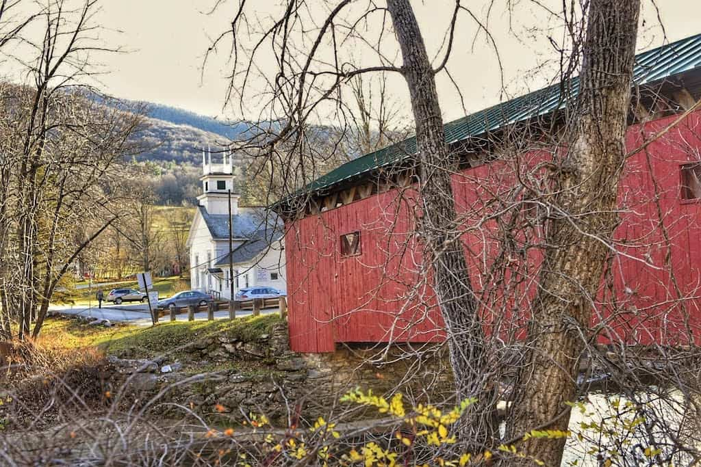 The Arlington Green Covered Bridge on a beautiful fall day in Vermont. You can see the historic church in the background.