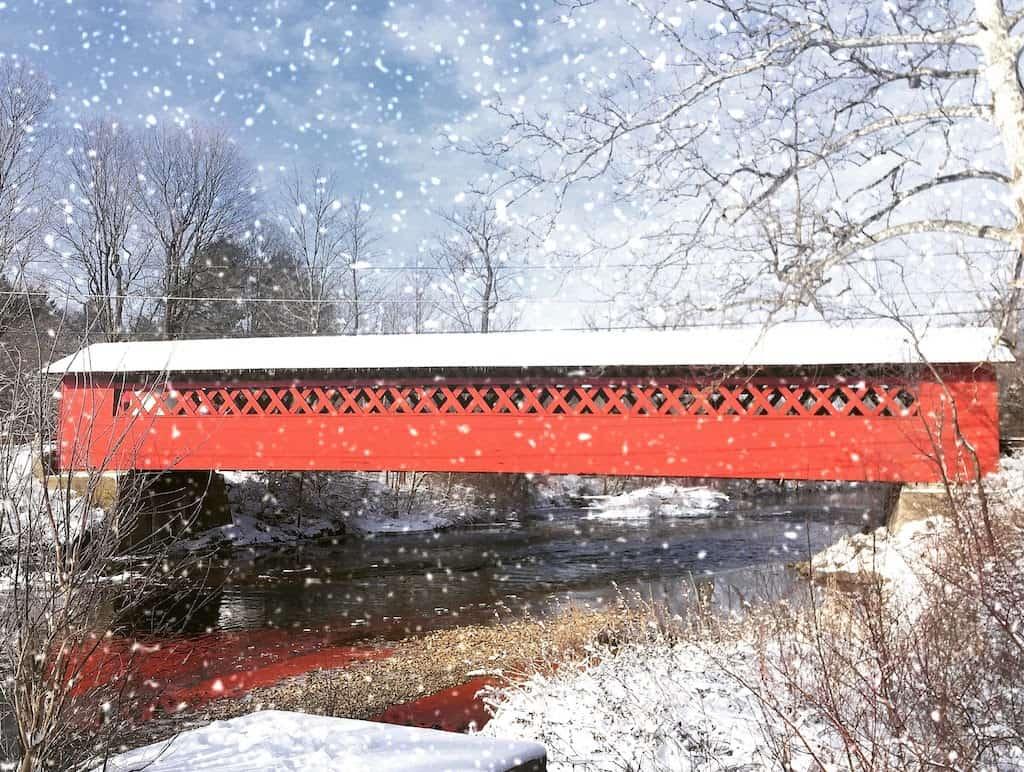 Snow gently falls around the Burt Henry Covered Bridge in Bennington, VT.