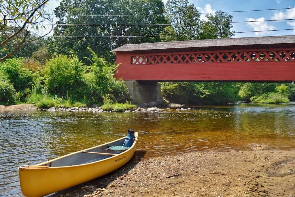 A yellow canoe is beached underneath the Burt Henry Covered Bridge in North Bennington, VT.