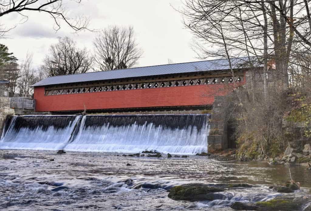 A dam and waterfall running underneath the Paper Mill Village Bridge in Bennington, VT.