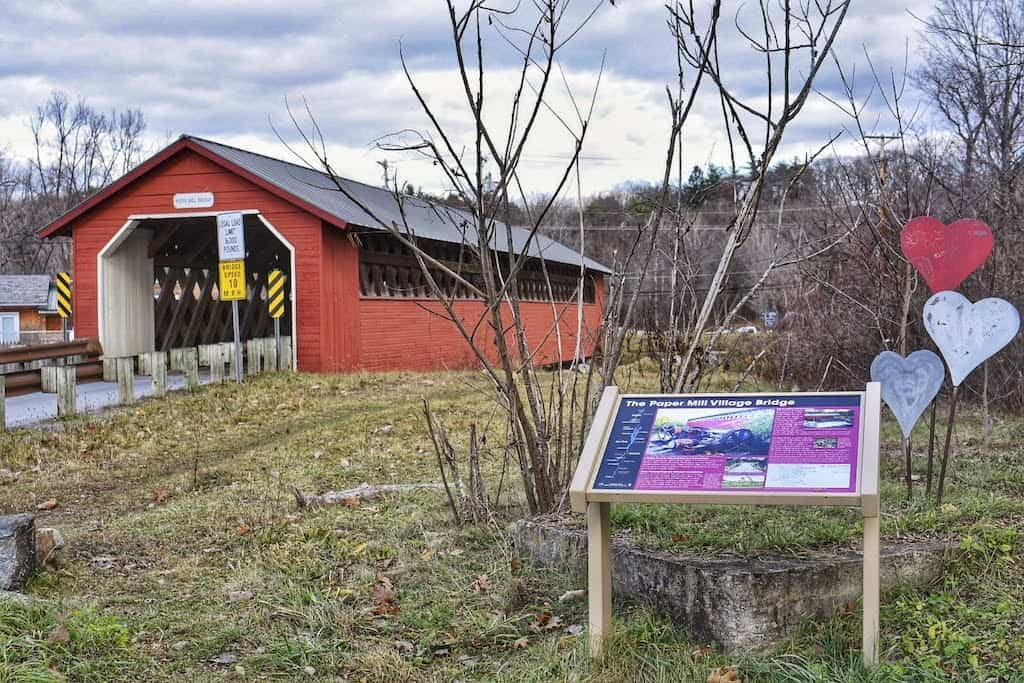 The Paper Mill Village Bridge and an informational sign in front of it. Bennington, Vermont.