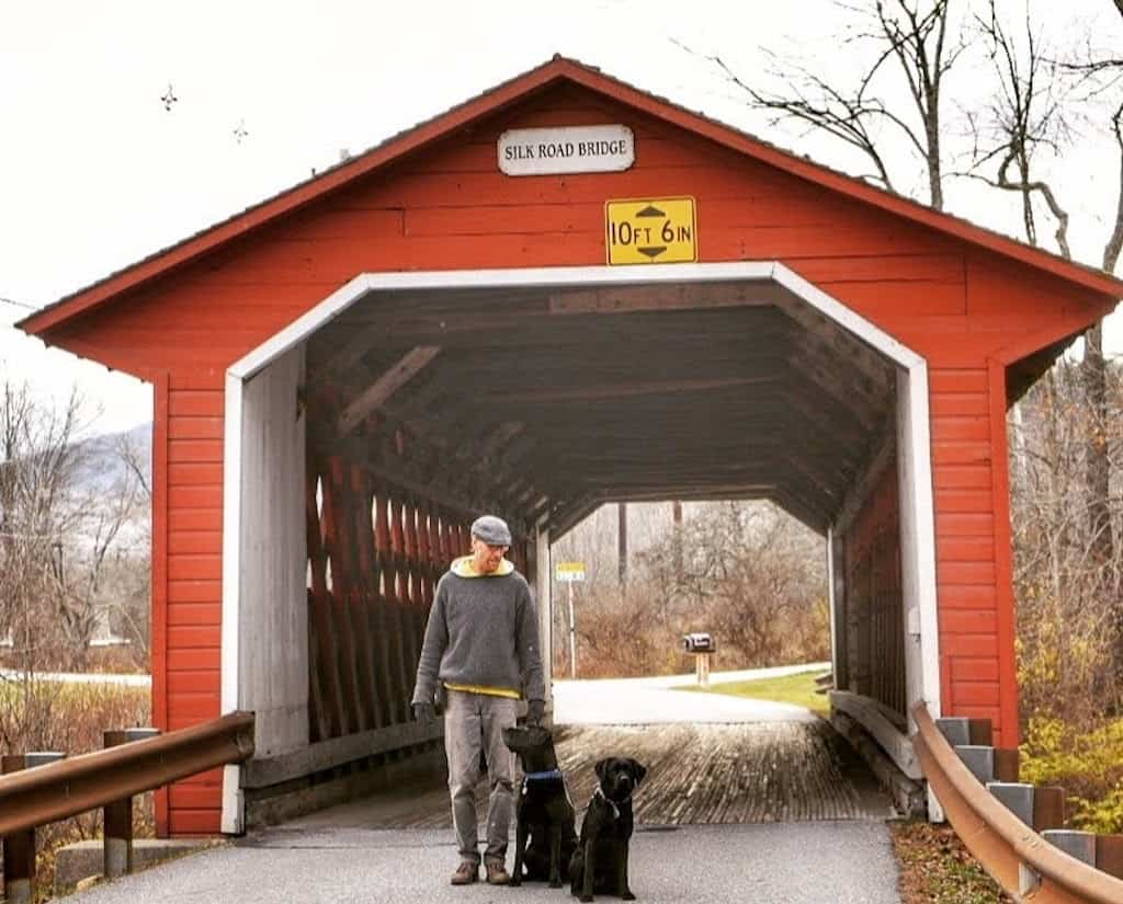 A man stands with two black labs in front of the Silk Road Covered Bridge in Bennington, Vermont.