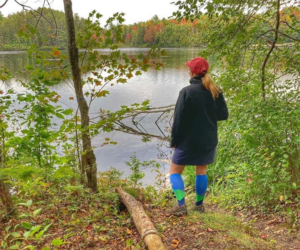A woman stands looking out at the view over Spectacle Pond in Brighton State Park, Vermont.