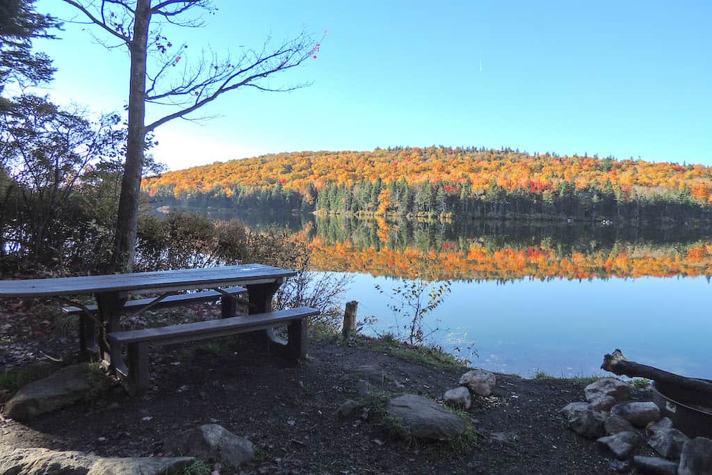 A fall foliage view from one of the waterfront campsites on Grout Pond in Vermont.