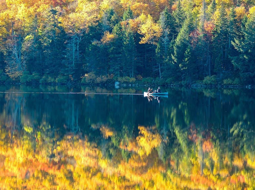 A fall foliage view of a canoe paddling the calm waters of Grout Pond in Vermont.