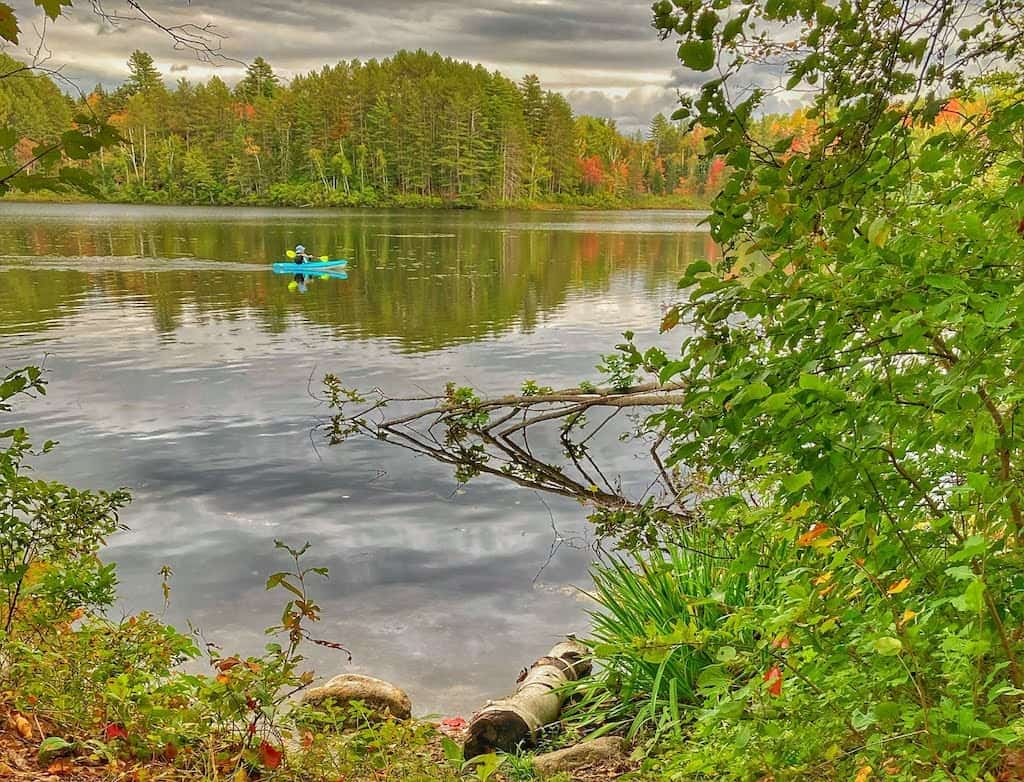 A woman paddles a canoe on Spectacle Pond in Brighton State Park, Vermont during the fall.