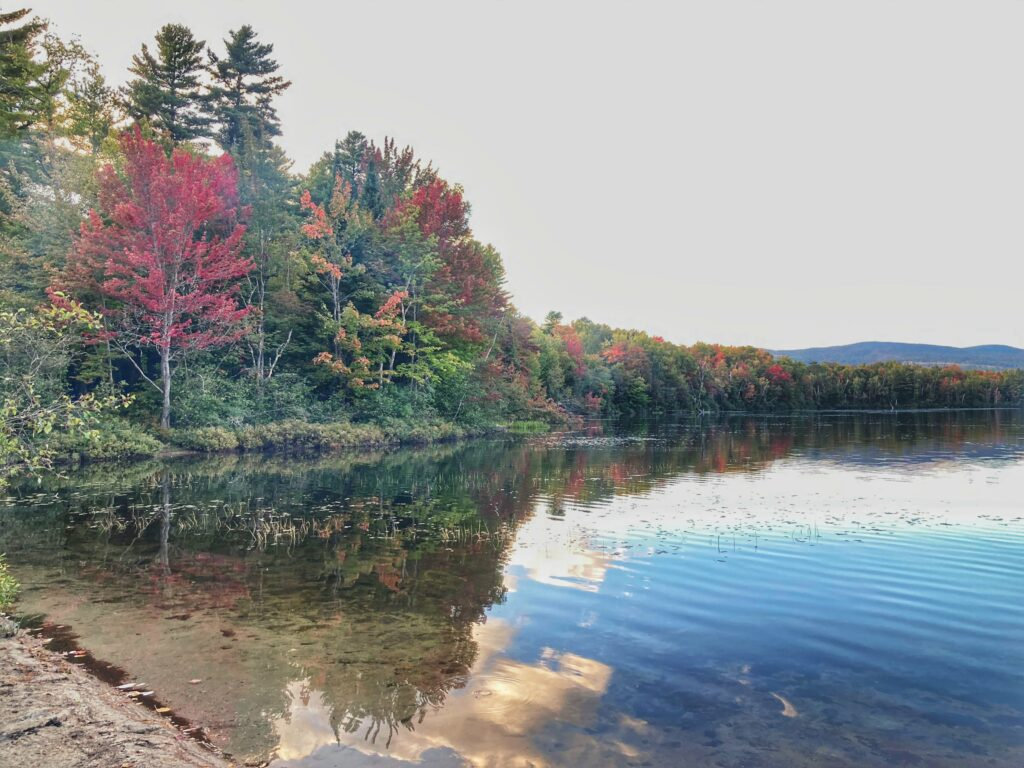 An autumn view of Spectacle Pond from the beach at Brighton State Park in Vermont.