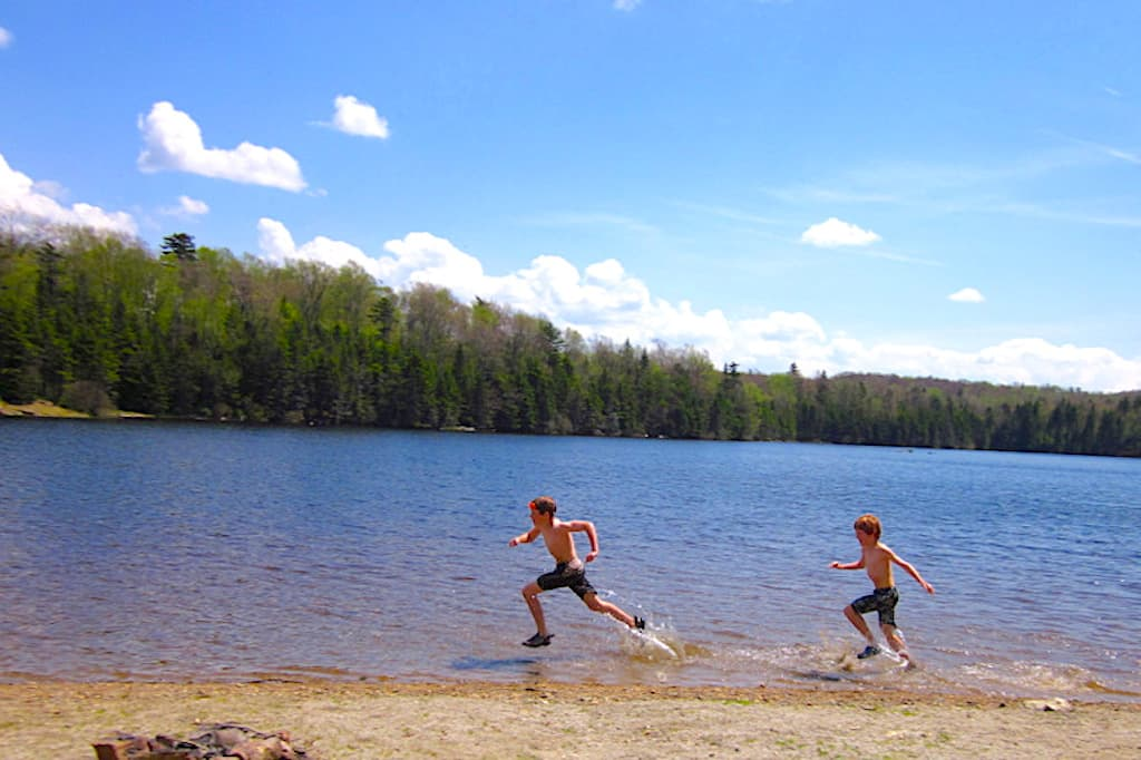Two boys running through the water on a sunny day at Woodford State Park in Vermont.