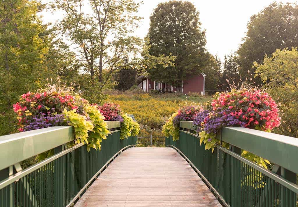 A footbridge with flowers on the railings that crosses the Deerfield River in Wilmington, VT