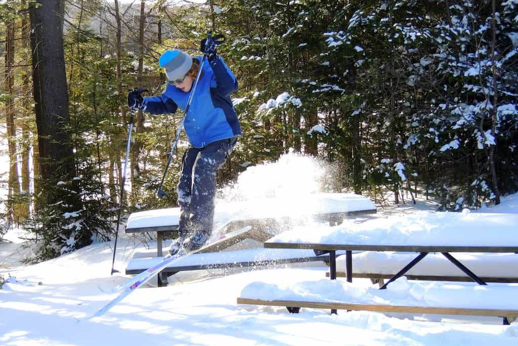 A boy uses a picnic table as a ski jump in Woodford State park, Vermont.