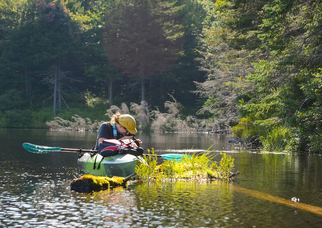 A woman sits in a kayak in the wetlands at Woodford State Park in Vermont.