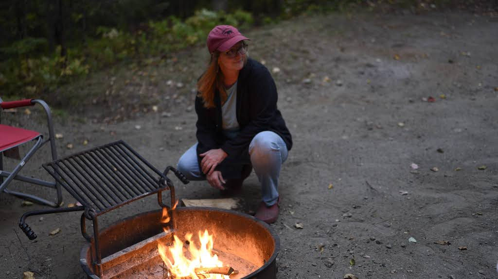 A woman sits next to a campfire in Vermont State Parks.